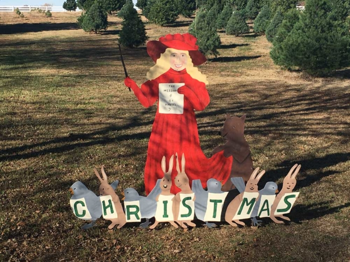 Christmas sign featuring rabbits and a caroler